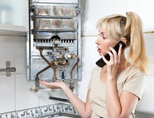 Blonde woman on phone talking to engineer about broken boiler